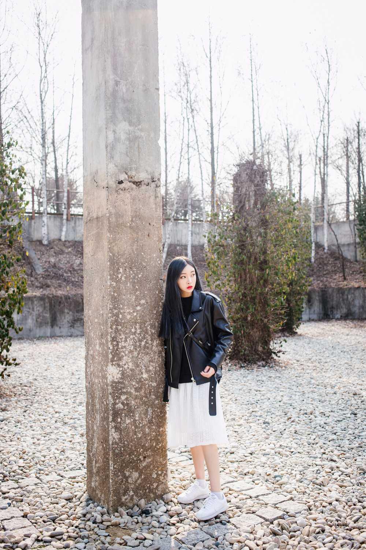 黑色皮衣外套,搭配白紗裙、白球鞋,性感又可愛著。